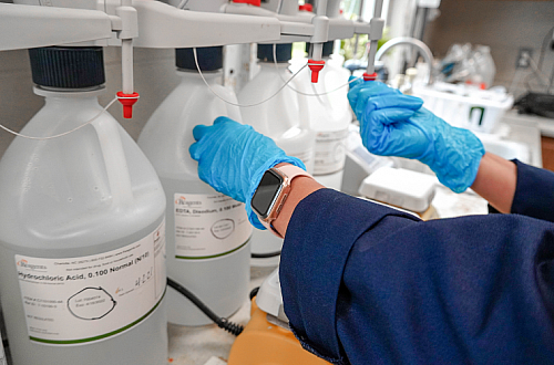 Large jugs filled with clear lab chemicals