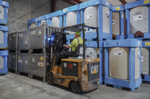 Employee on forklift placing containers of chemicals