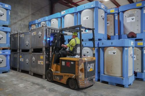 Employee driving forklift with chemicals