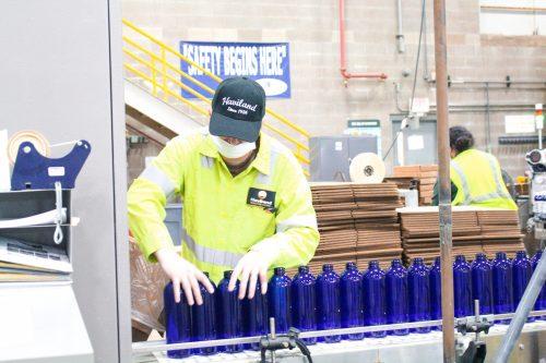 Employee preparing bottles for filling