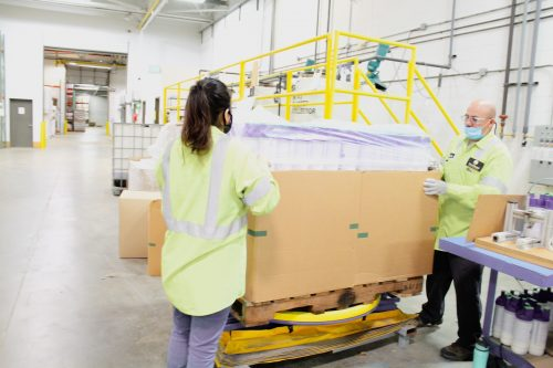 Employees sealing skids for shipping