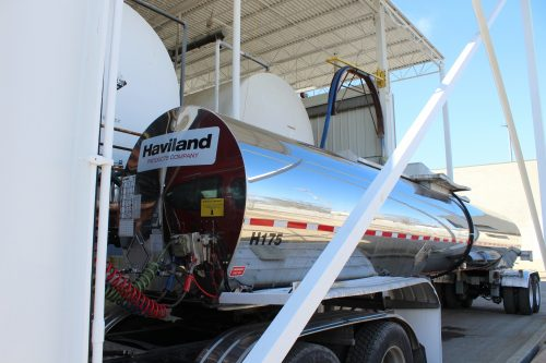 Metallic semi truck being filled with product