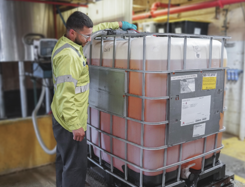 Employee filling liquid chemical into container