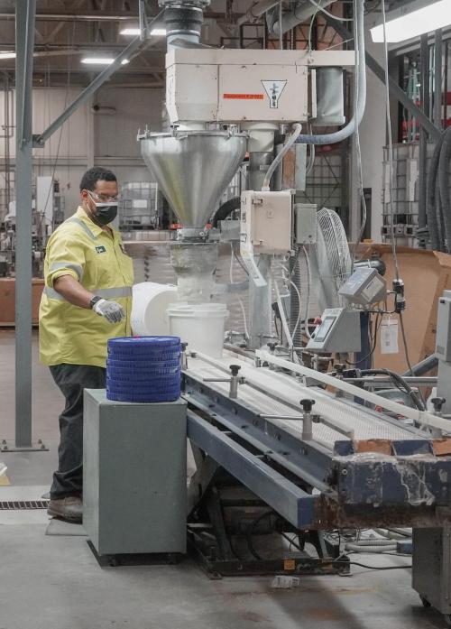 Employee preparing pails on filling line