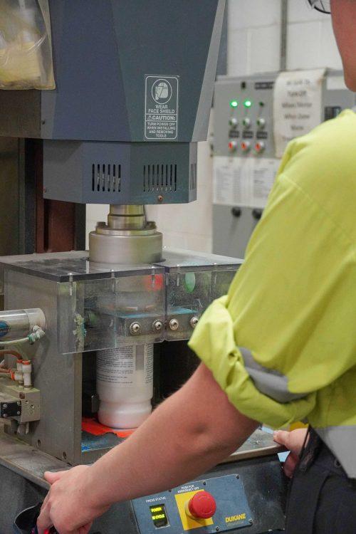 Employee sealing lid onto bottle